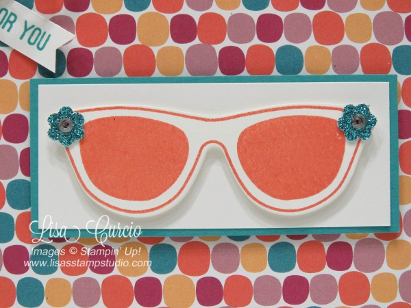 These sunglasses boast flowers and rhinestones on a colorful background of designer paper and glimmer paper. Pocketful of Sunshine from Stampin' Up! Close up view of sunglasses.