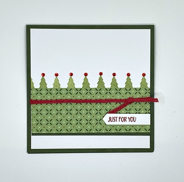 This Christmas card features pine trees